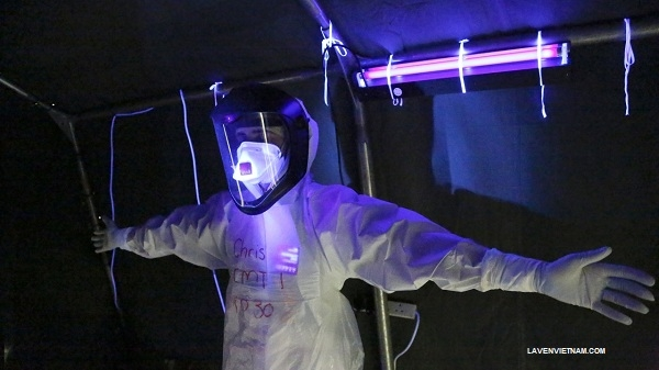Nhân viên y tế khử trùng đồ bảo hộ bằng đèn chiếu tia cực tím